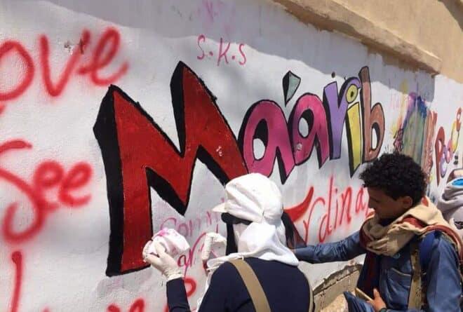 بين شعاري «النصر» و «الهزيمة» شابة يمنية تبرز شعار «السلام» في مأرب